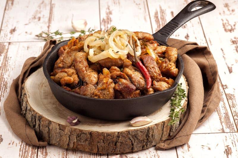 Stekt griskött med lökar och varm peppar arkivfoto