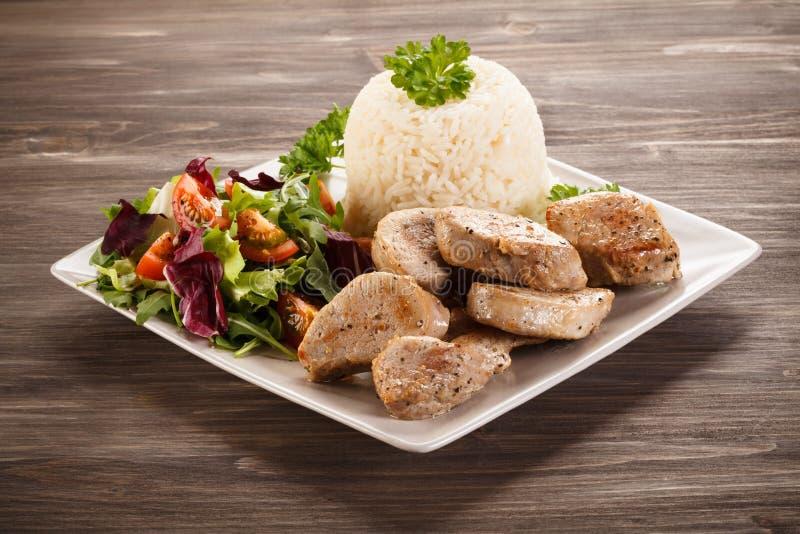 Stekt grisköttfransyska, vita ris och grönsaksallad royaltyfri bild