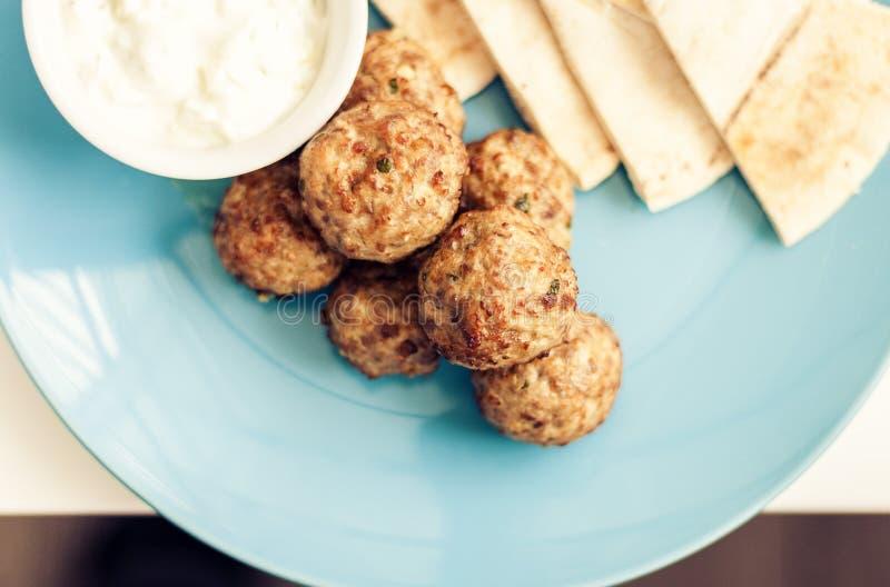 Stekt k?ttf?rs med s?s och tortillor, traditionell grekisk lunch p? en bl? platta i en restaurang royaltyfri foto