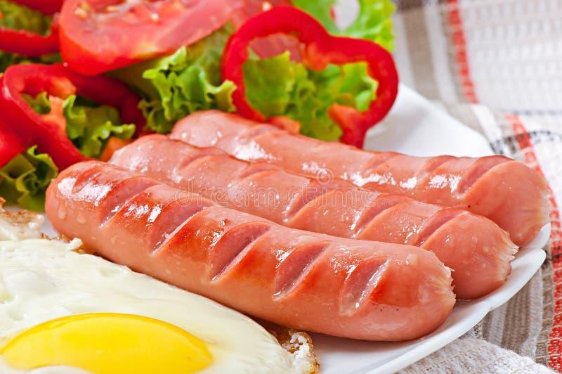 Stekt korv, ägg och blandad sallad arkivfoton