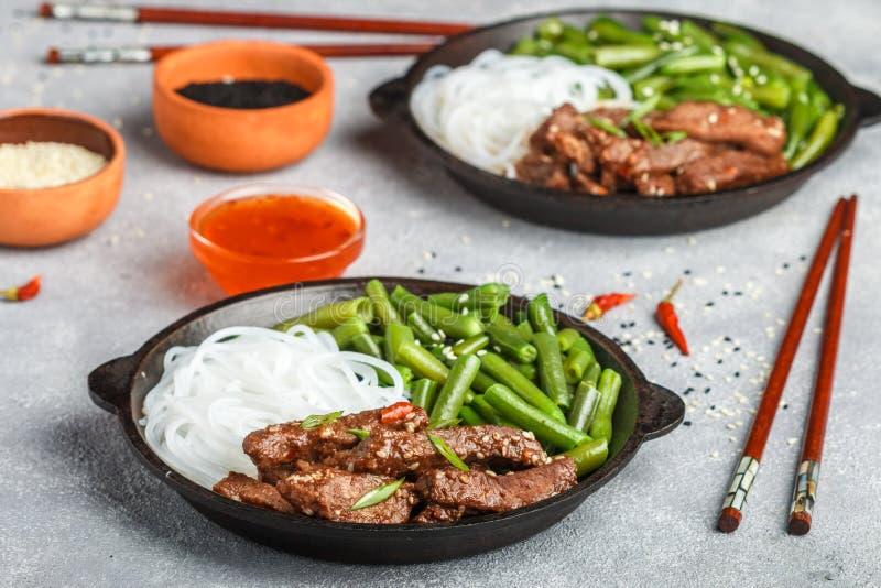 Stekt kryddigt nötkött med sesamfrö, haricot vert och risnudlar arkivfoto