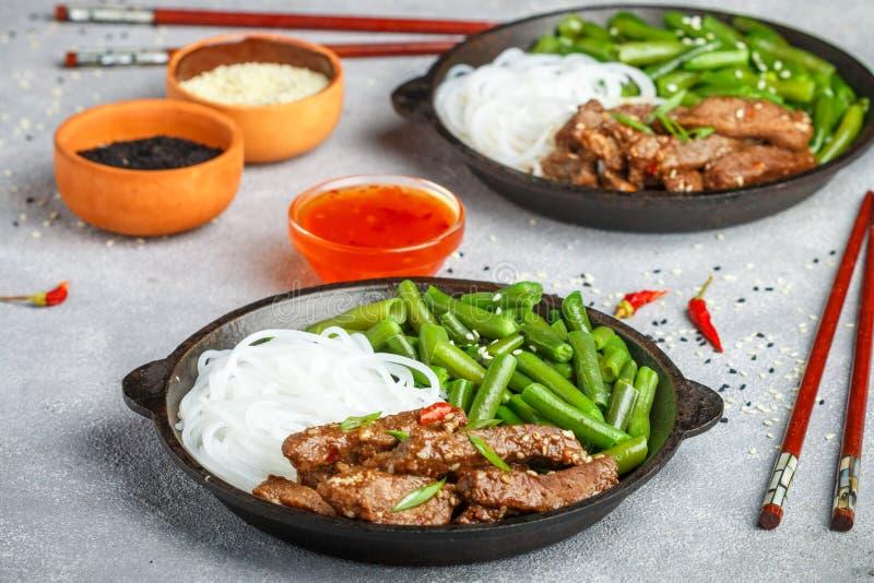 Stekt kryddigt nötkött med sesamfrö, haricot vert och risnudlar arkivfoton