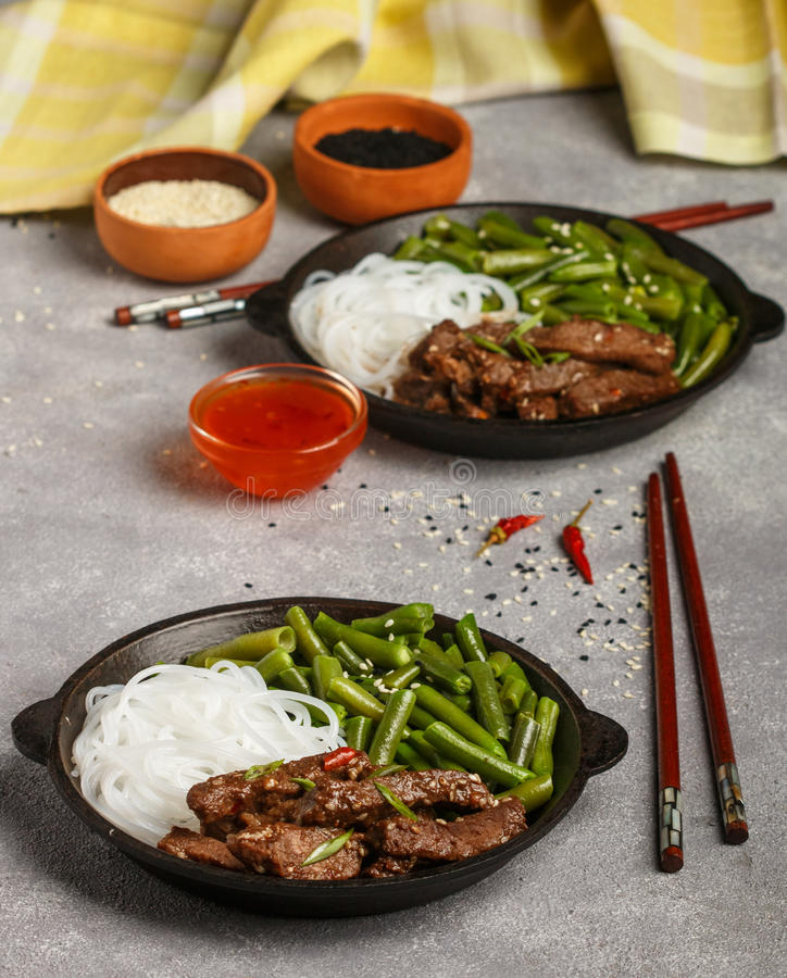 Stekt kryddigt nötkött med sesamfrö, haricot vert och risnudlar fotografering för bildbyråer