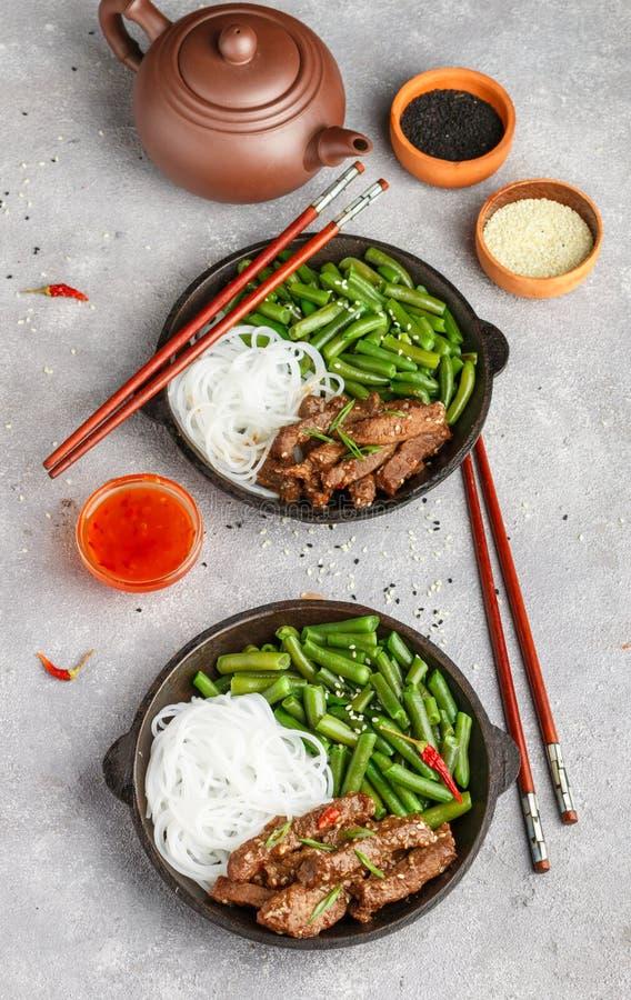 Stekt kryddigt nötkött med sesamfrö, haricot vert och risnudlar royaltyfri foto