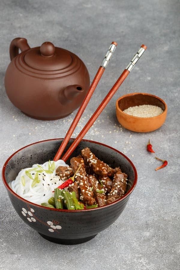 Stekt kryddigt nötkött med sesamfrö, haricot vert och risnudlar royaltyfri bild