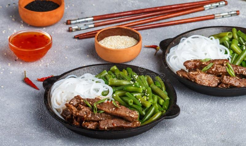 Stekt kryddigt nötkött med sesamfrö, haricot vert och risnudlar royaltyfria foton