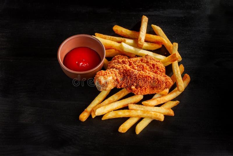 Stekt kyckling med franska småfiskar, skräpmat och sjuklig mat royaltyfri fotografi