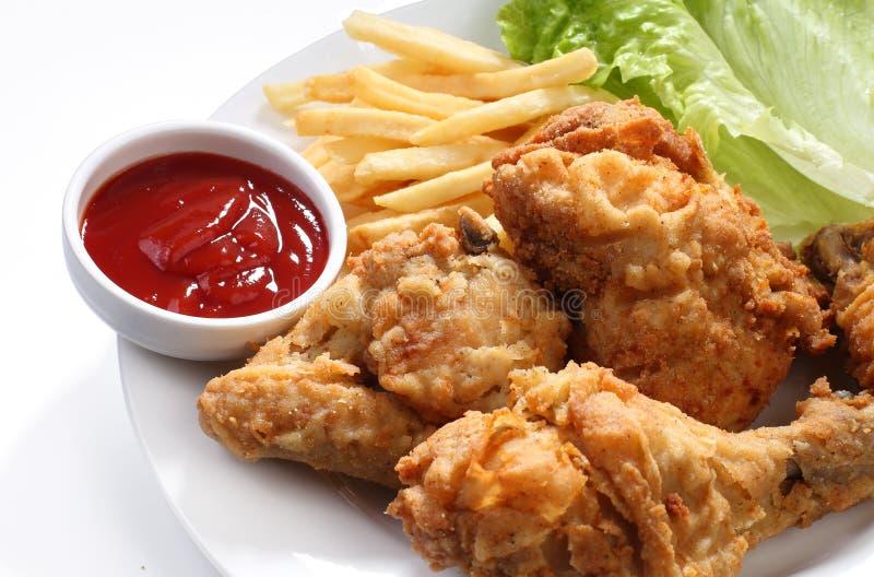 Stekt kyckling och småfiskar med ketchup royaltyfria bilder