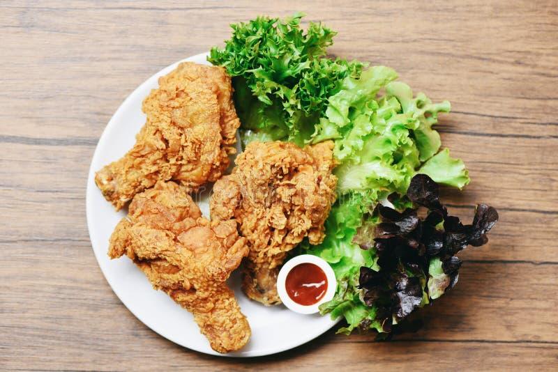 Stekt kyckling som ?r frasig p? den vita plattan med ketchup- och salladgr?nsallatgr?nsaken p? tr? arkivbilder