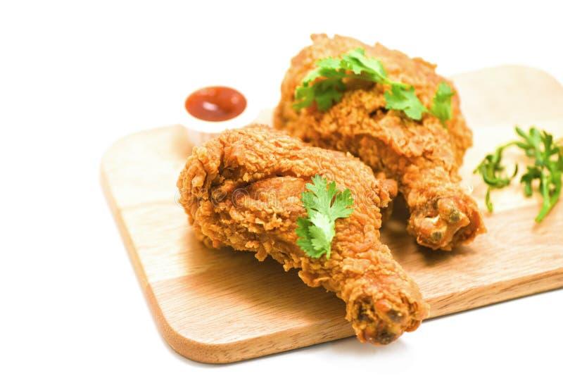 Stekt kyckling som är frasig på plattaträbräde med ketchup på vit arkivbild