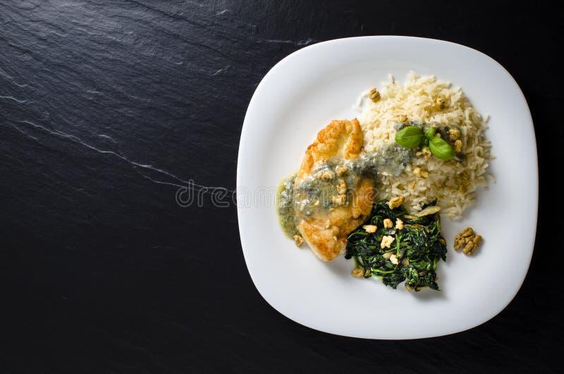Stekt kycklingbröst med spenat, ris och gorgonzola sås royaltyfria bilder