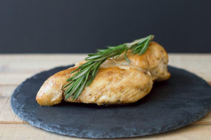 Stekt kycklingbröstet med nya rosmarin på litet kritiserar brädet fotografering för bildbyråer
