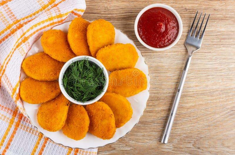 Stekt kycklingklumpar, bunke med dill i platta på servett, bunke med ketchup, gaffel på tabellen Top beskådar fotografering för bildbyråer