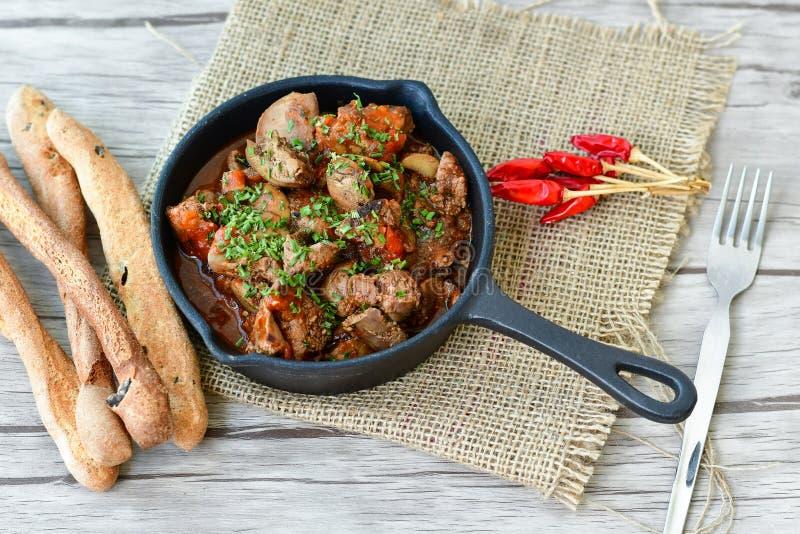 Stekt kycklinglever med Mushroomsin den järn- pannan arkivfoto