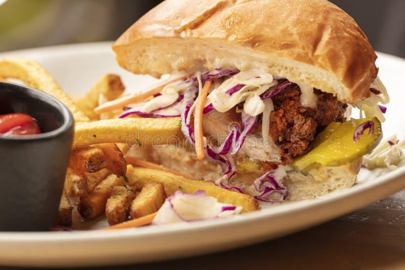 Stekt kycklingsmörgås på en hamburgarebulle och en sida av franska småfiskar och ketchup arkivfoton