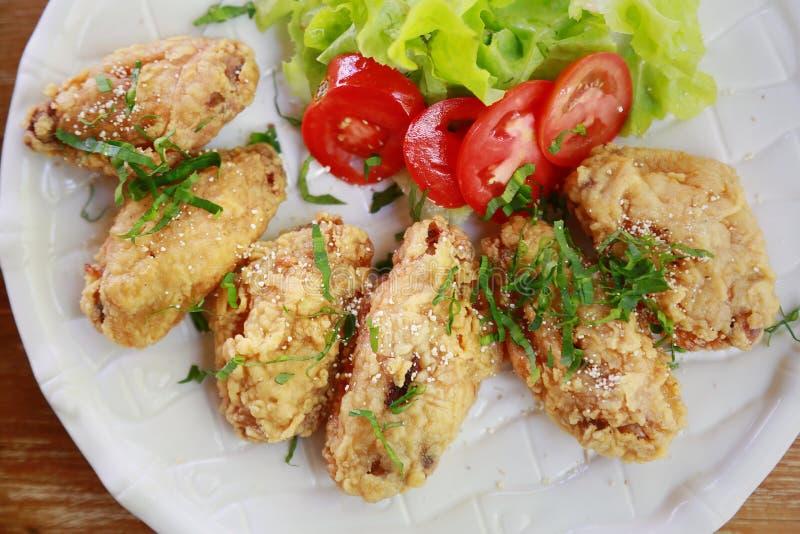 Stekt kycklingvingar eller stekt kyckling med grönsaken och sås på den vita maträtten stekt kyckling är dålig kolesterol och bad  arkivfoto