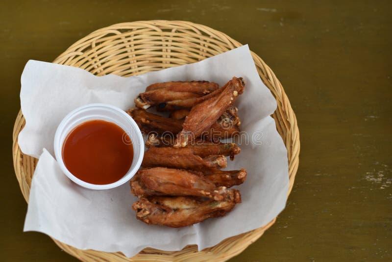 Stekt kycklingvingar med dopp i en korg royaltyfri bild