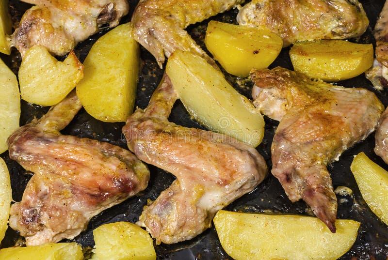 Stekt kycklingvingar med potatisar arkivbild