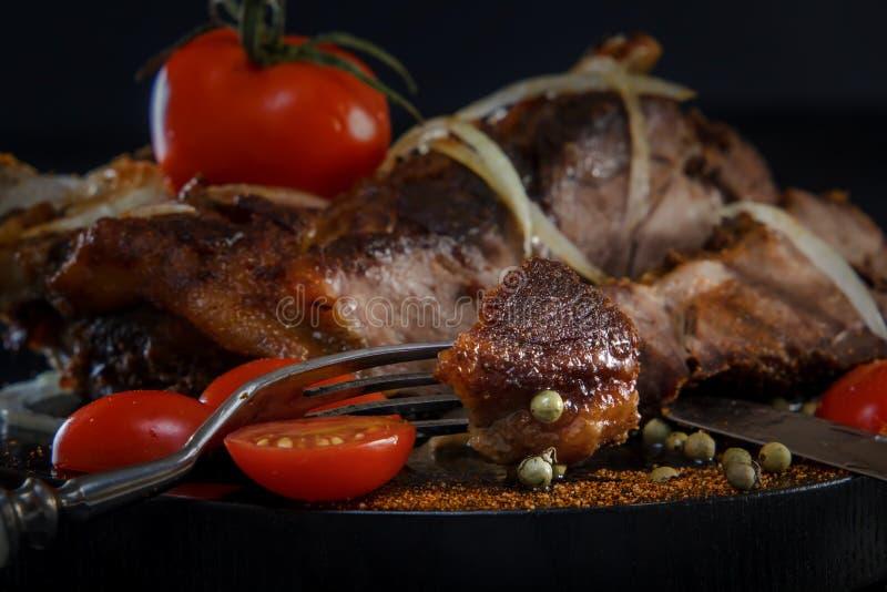 Stekt lamm med grönsaker Stekt kött på en svart bakgrund Stycke av kött på gaffeln fotografering för bildbyråer