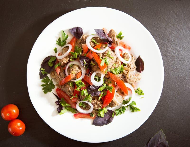 Stekt lever med löken och tomater på den svarta stenen royaltyfria foton