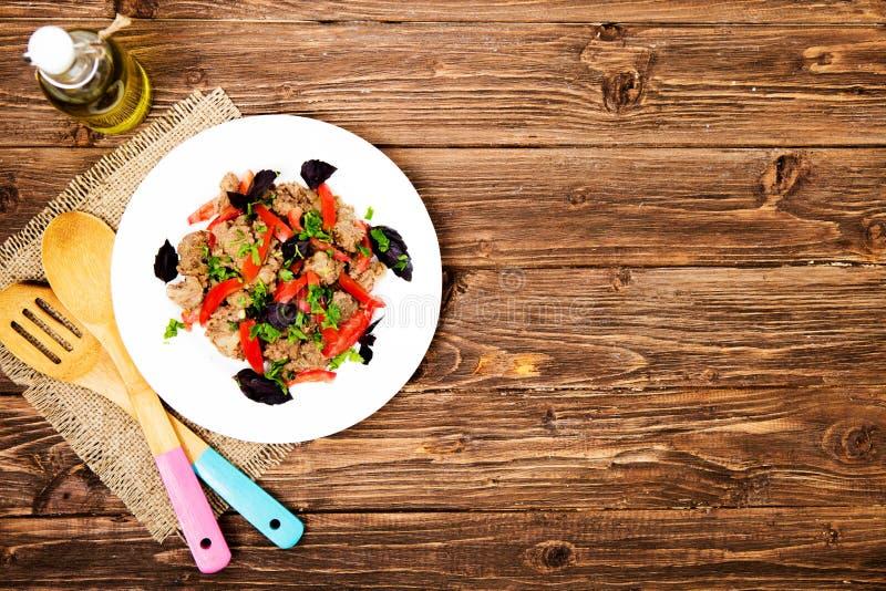 Stekt lever med löken och tomater på träbakgrund royaltyfri bild