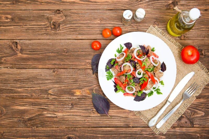 Stekt lever med löken och tomater på träbakgrund royaltyfria foton