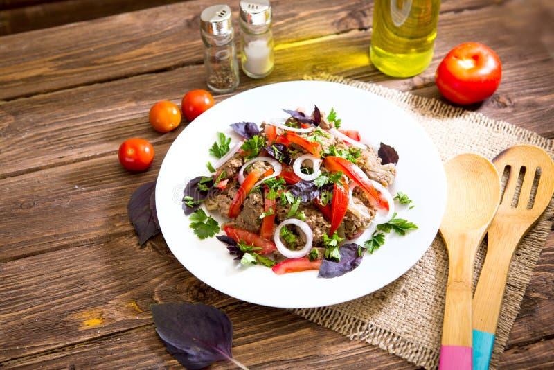 Stekt lever med löken och tomater på träbakgrund royaltyfri foto