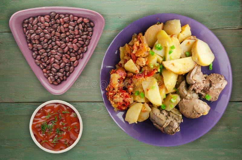 Stekt lever med potatisar och lät småkoka tomater royaltyfri fotografi