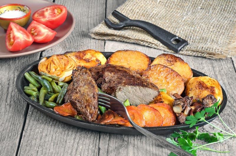 Stekt nötköttlever med grönsaker på en panna royaltyfri foto