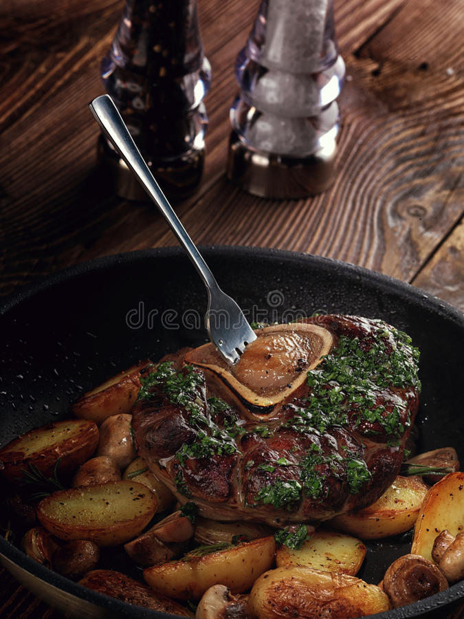 Stekt ossobuco med grönsakragu av potatisar och champinjoner royaltyfria bilder