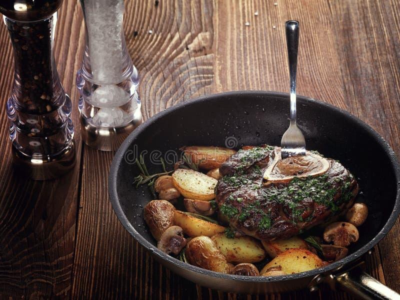 Stekt ossobuco med grönsakragu av potatisar och champinjoner royaltyfri bild