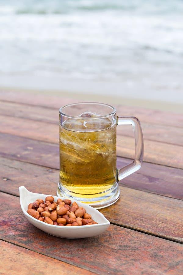Stekt peeljordnötter och öl royaltyfria foton