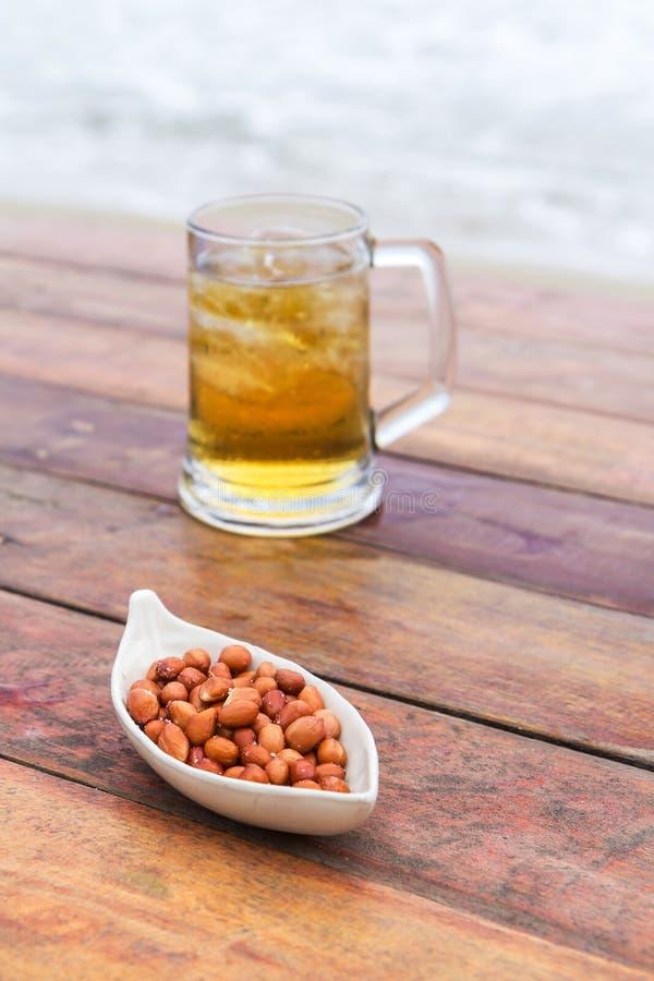 Stekt peeljordnötter och öl royaltyfri bild
