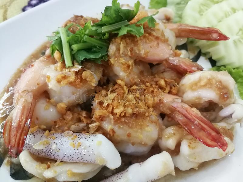 Stekt räka och tioarmad bläckfisk med vitlökpeppar på den platta/Thai maten arkivfoton