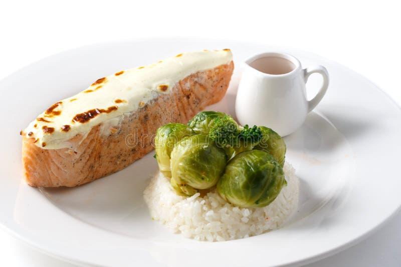 Stekt röd fiskbiff i den vit krukan, ris, kål och sås i en vit platta på en isolerad vit bakgrund royaltyfri fotografi