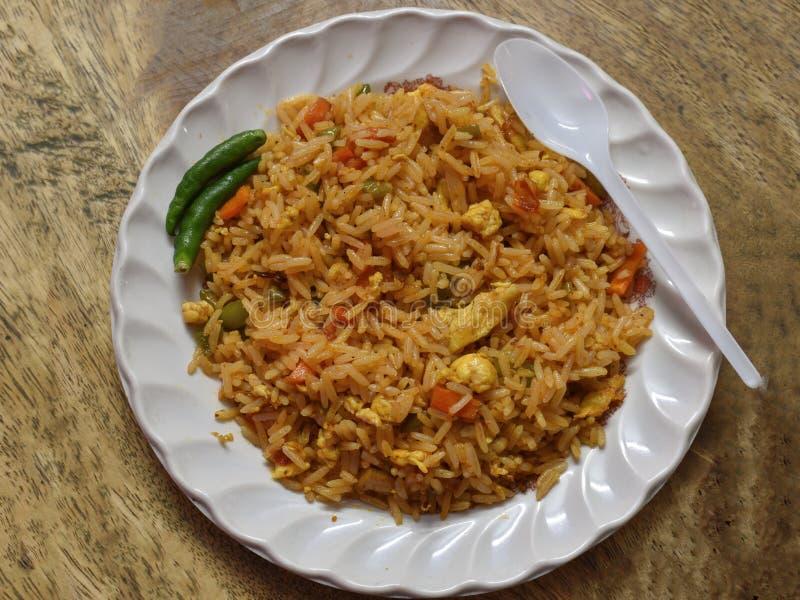 Stekt ris är en maträtt av lagat mat ris, som har stekts under omrörning i för att woka, eller en stekpanna och blandas vanligt m royaltyfria foton