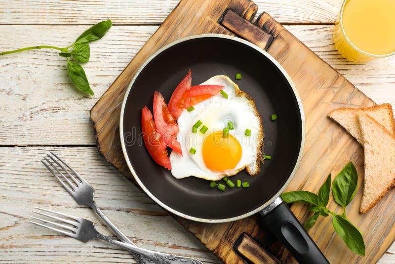 Stekt solig sida upp ägget med tomaten i pannan som tjänas som på tabellen royaltyfri fotografi