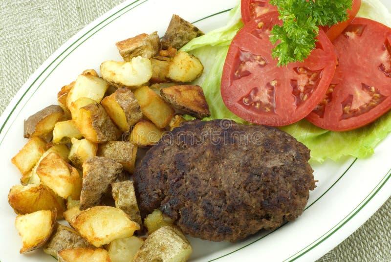 stekt steak för hamburgareutgångspunktpotatisar arkivbild