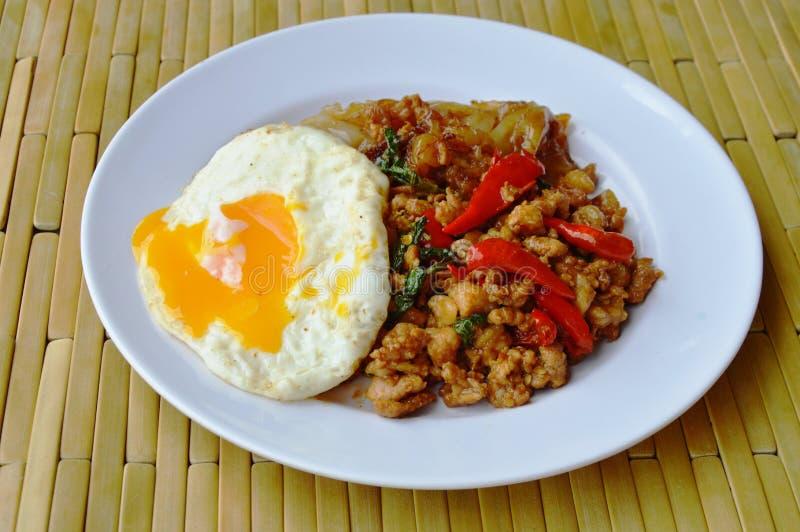 Stekt stor nudel och kryddigt finhackat griskött med ägget för basilikabladtoppning royaltyfri bild
