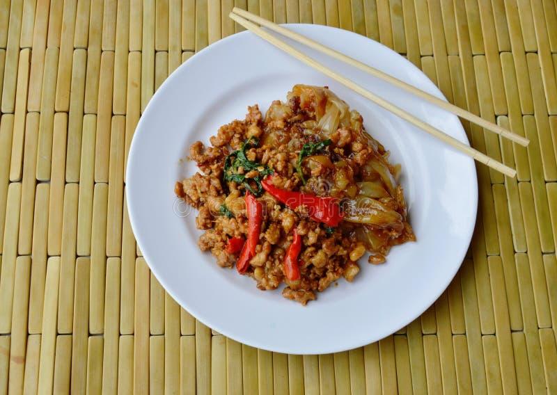 Stekt stor nudel och kryddigt finhackat griskött med basilikabladet på maträtt arkivbild