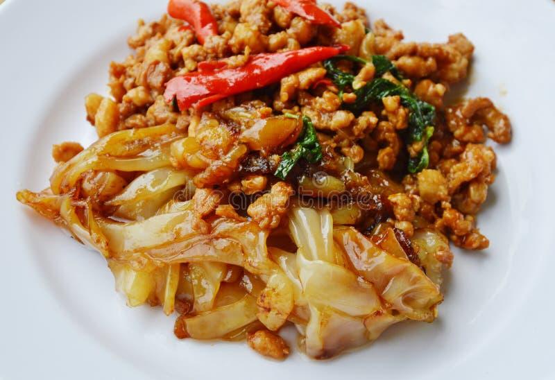 Stekt stor nudel och kryddigt kotlettgriskött med basilikabladet på maträtt arkivfoton
