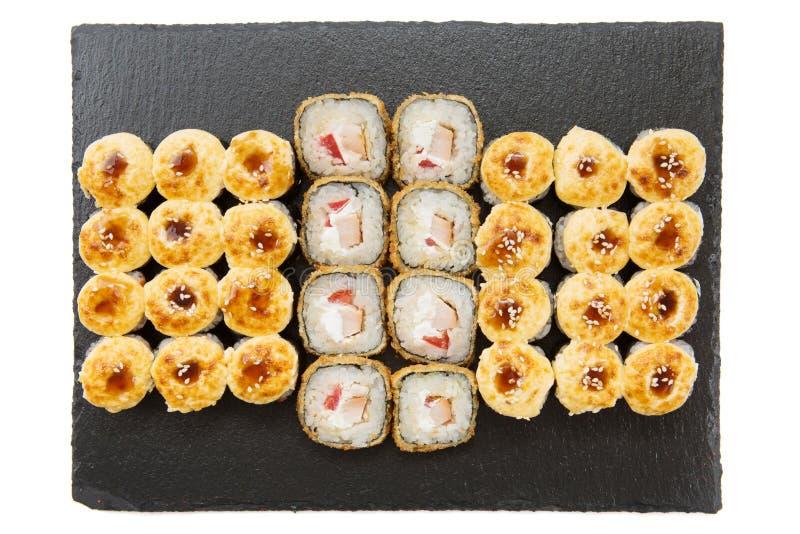 Stekt sushirulle med sås på den mörka stenen traditionell matjapan Japanska rullar för kokkonsttempurasushi arkivfoton