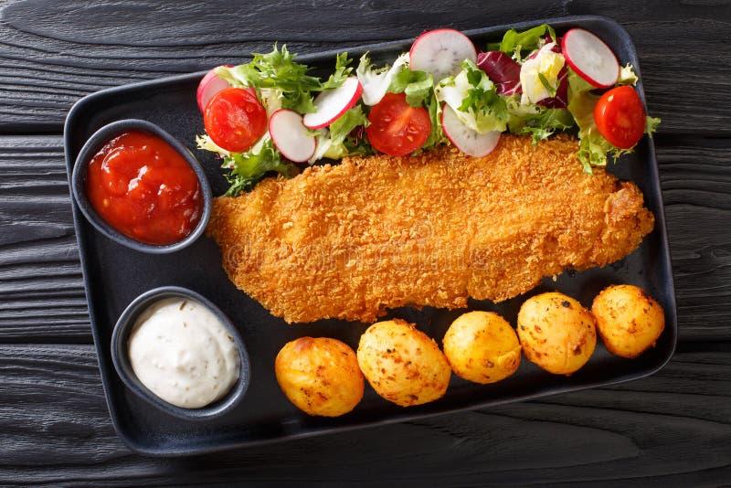 Stekt torskfil?, i att panera med en garnering av nya potatisar och salladn?rbilden f?r ny gr?nsak p? tabellen horisontalb?sta si royaltyfri bild