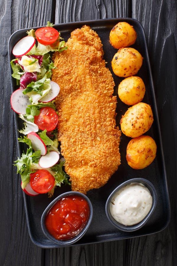 Stekt torskfil?, i att panera med en garnering av nya potatisar och salladn?rbilden f?r ny gr?nsak p? tabellen Vertikal b?sta sik arkivbild