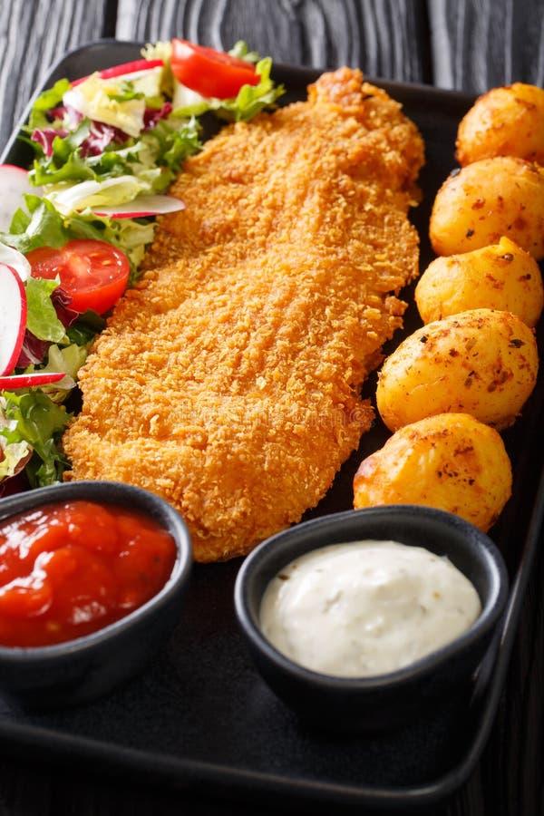 Stekt torskfil?, i att panera med en garnering av nya potatisar och salladn?rbilden f?r ny gr?nsak p? tabellen vertikalt royaltyfri fotografi