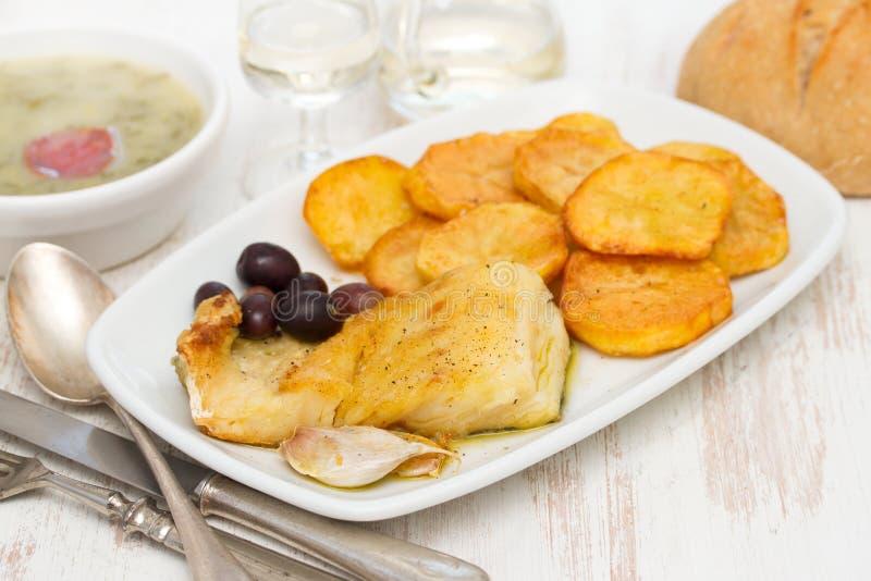 Stekt torskfisk med potatisen på den vita maträtten royaltyfria foton