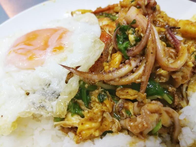 Stekt under omrörning stekt skaldjur i gul curry eller, serve med stekt eg. royaltyfri bild