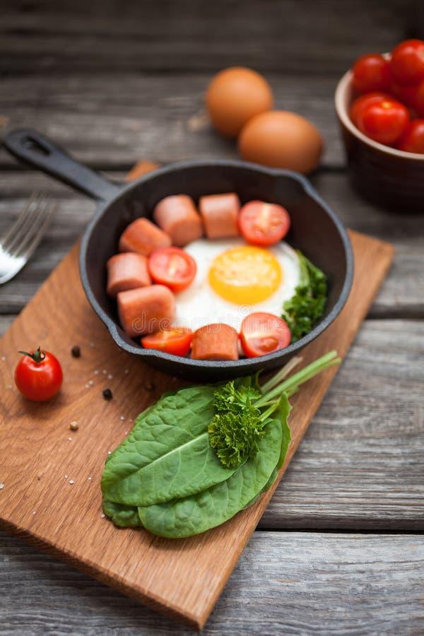 Stekte ägg i en stekpanna med korvar, körsbärsröda tomater, örter, kryddor och bröd för frukost fotografering för bildbyråer