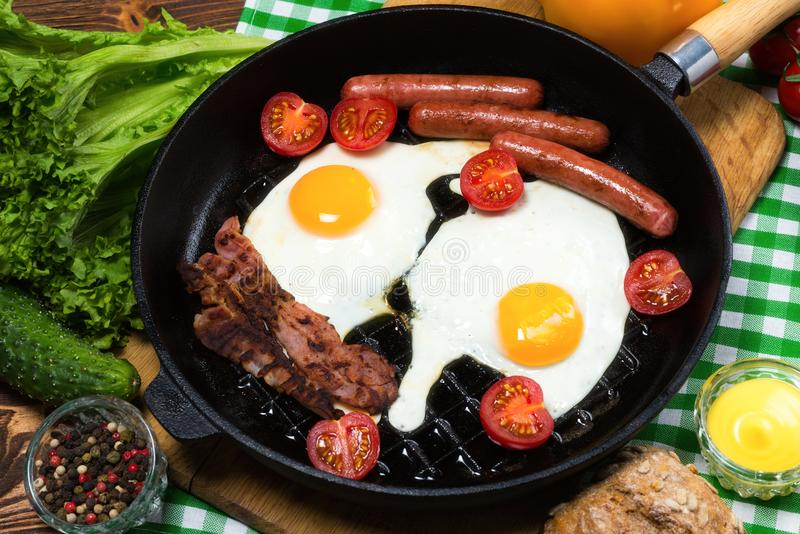 Stekte ägg med bacon och korvar i en stekpanna royaltyfri bild
