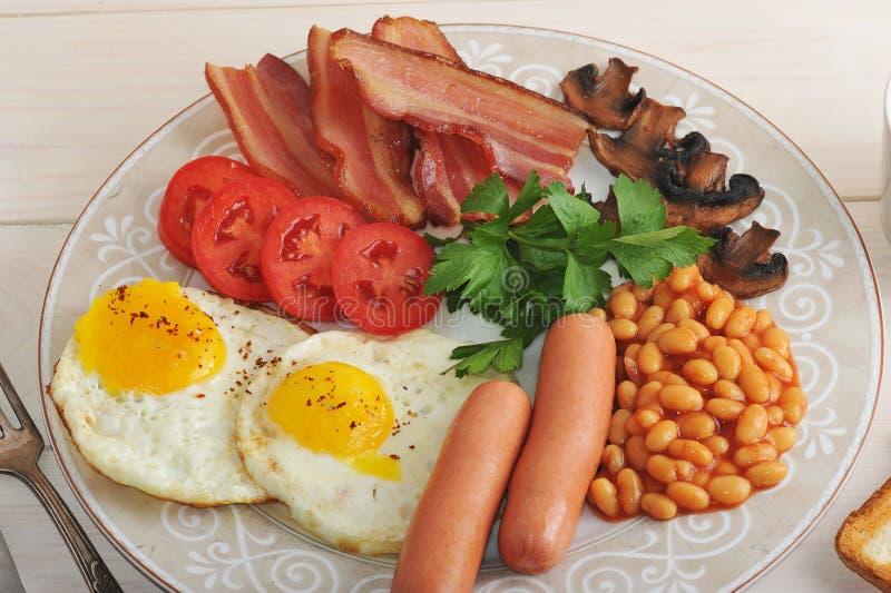 Stekte ägg med bacon, tomater, bönor, champinjoner och korvar royaltyfri fotografi